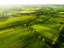 Aerial View Of Endless Lush Pastures And Farmlands Of Ireland. Beautiful Irish Countryside With Emerald Green Fields And Meadows.