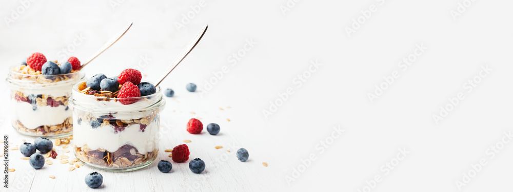 Fototapeta Two jars with tasty parfaits made of granola, berries and yogurt on white wooden table. Shot at angle with place for text, banner.
