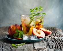 Refreshing Iced Tea With Ripe Peaches On Rustic Background, Selective Focus, Toned Image