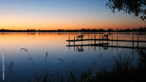 Bemidji, Minnesota, the Best Town in Minnesota is seen across Lake Irving, the first lake on the Mississippi River, after sunset in summertime Wallpaper Mural