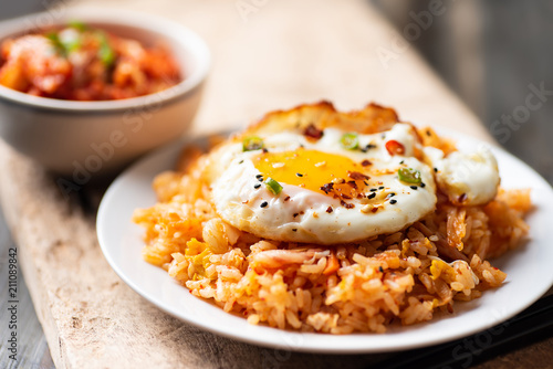 Kimchi fried rice with fried egg on top and fresh kimchi cabbage, Korean food