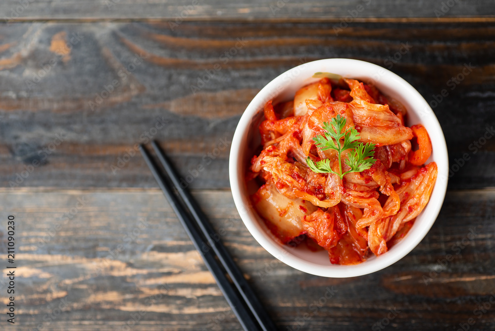 Fototapeta Kimchi cabbage in a bowl with chopsticks for eating on wooden background, top view, Korean food