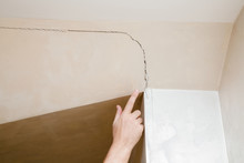 Man's Hand Finger Pointing To The Cracked Wall In House. Building Problems And Solutions Concept.