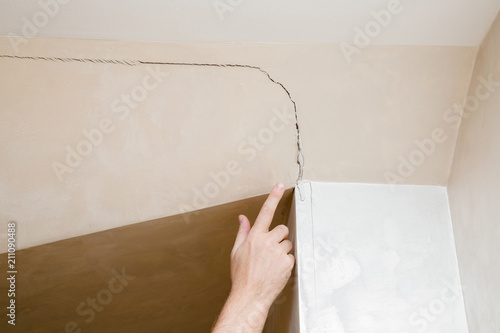 Láminas  Man's hand finger pointing to the cracked wall in house