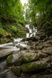 Beautiful mountain rainforest waterfall with fast flowing water and rocks, long exposure.