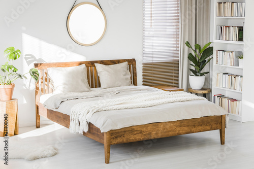 White Bedroom Interior With Wooden King Size Bed, Fresh Green Plants,  Window With Blinds And Library On White Rack