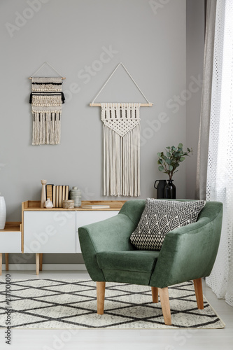 Fotografering  Real photo of a boho living room interior with macrame hanging on gray wall behi