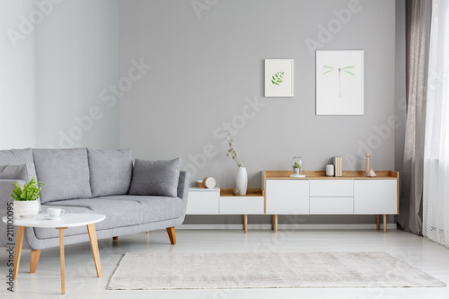 Obraz Real photo of a spacious living room interior with gray sofa standing between a wooden table and white cupboards - fototapety do salonu