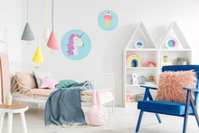 Furry Pink Pillow On A Vibrant Blue Armchair In A Sweet Kid Bedroom Interior With Cozy Bedding And Cartoon Posters On White Walls