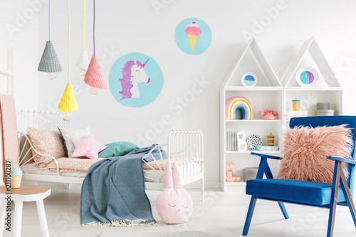 Fotografía  Furry pink pillow on a vibrant blue armchair in a sweet kid bedroom interior wit