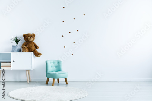 Fényképezés  Small light blue armchair for kid standing in white room interior with stars on the wall, white rug and cupboard with books, teddy bear and fresh plant