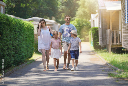 Family walking in camp village during holidays Poster Mural XXL