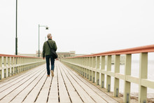 Rear View Of Senior Man Walking On Wooden Pier Against Clear Sky