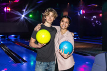 Portrait Of Smiling Multi-ethnic Teenage Friends Standing With Balls At Bowling Alley