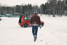 Rear View Of Man Walking Towards Red Car On Snow Covered Landscape