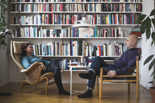 Full Length Of Therapist And Patient Discussing By Bookshelf At Home Office