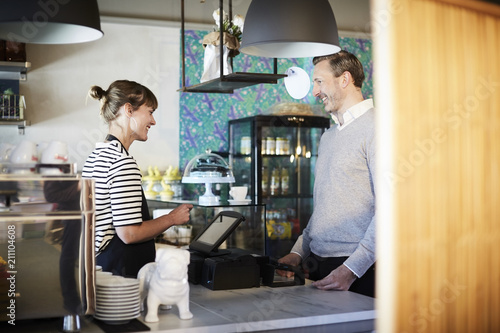 Smiling barista talking to customer while using cash register at checkout counter in cafe