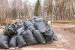 Close-up of black trash bags piled up In the city park.