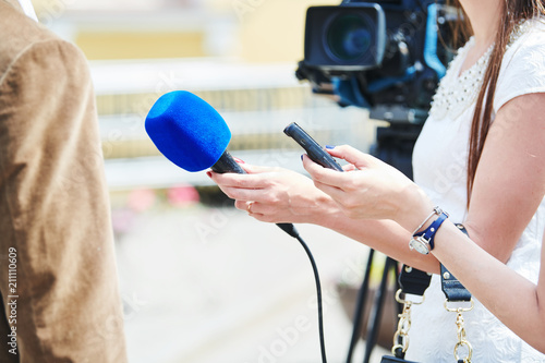 Fotografía News comment. reporter with microphone making interview