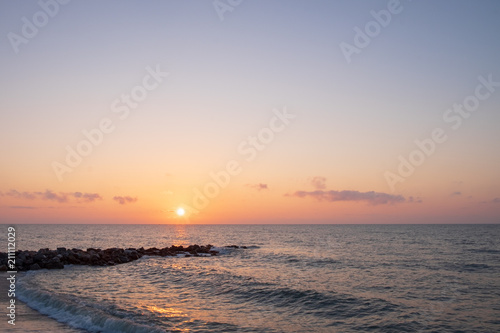 Spoed Foto op Canvas Zee zonsondergang At the beach with rocks jutting out into the sea at the time of sunrise or sunset