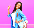 canvas print picture - Happy young african woman with backpack over pink background