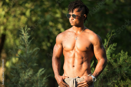 Fotografie, Obraz  African macho muscular man bodybuilder topless with naked torso in a park