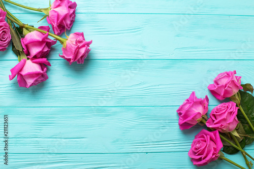 Photo  Border from pink  roses  flowers on teal  color wooden background