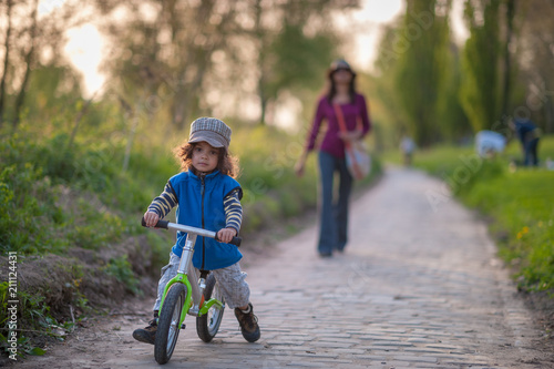 Fotografie, Obraz  Boy on wheel bike at outdoor walk with mom