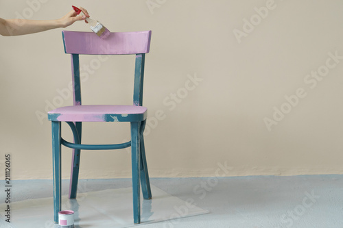 woman's hand painting chair in pink at home