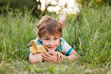 The Little Smiling Child Boy With Ducklings Lies In A Grass In The Summer