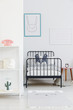 Child's bed with black metal frame in a small, simple bedroom interior. Rabbit poster on a white wall. Real photo