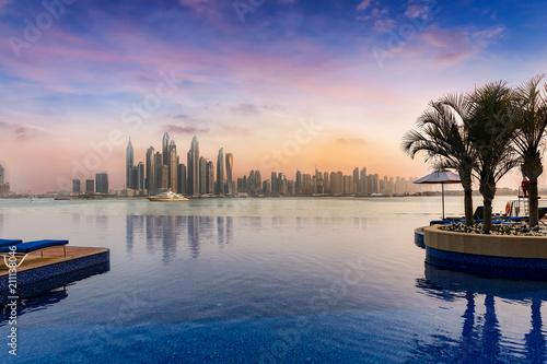 obraz dibond Blick auf Dubai Marina bei Sonnenuntergang mit einem Swimming Pool im Vordergrund