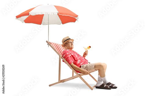 Fotografering Elderly tourist holding a cocktail and sitting in a deck chair with an umbrella