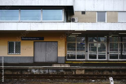 Poster Treinstation Leerstehendes Bahnhofsgebäude / Ein leerstehendes Bahnhofsgebäude des Bahnhofes Niedernhausen mit vergitterten Fenstern sowie einer Klinkerfassade.