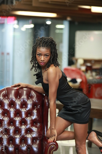 Alluring black woman on leather armchair Wallpaper Mural