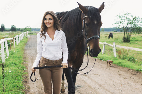Tablou Canvas Young woman rider and her beautiful horse
