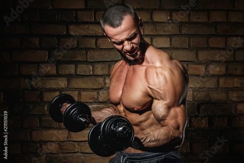 Bodybuilder doing exercises for biceps with a dumbbells Wallpaper Mural