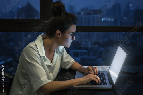 Photo  Woman is working with laptop at home during night.