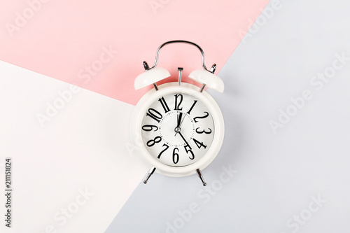 Photo White antique alarm clock on a three-color pink, gray and white background