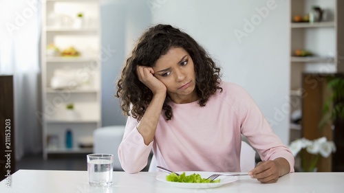 Sad lady in front of green salad plate and glass of water on table, weight loss Canvas Print