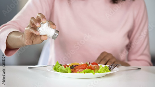 Fototapeta Woman adding too much salt to her food, unhealthy eating, dehydration problems obraz