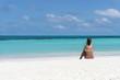 Junge Frau sitzend an weißem Sandstrand Blick zum Meer