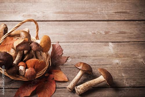 mushrooms in basket on wooden background