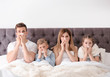 Family suffering from cold in bed at home