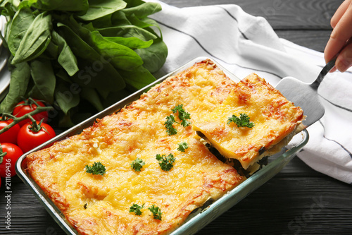 Woman holding spatula with piece of spinach lasagna in kitchen