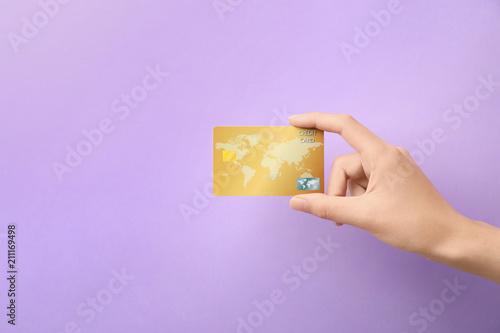 Woman holding credit card on color background