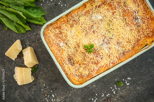 Baking dish of lasagna with spinach on grey background