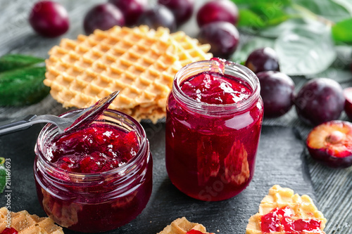 Glass jars with delicious homemade plum jam on table