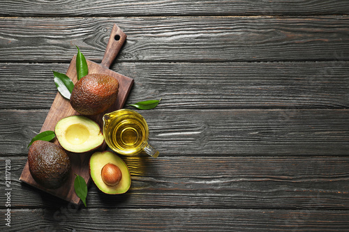 Gravy boat with oil and ripe fresh avocados on wooden table, top view