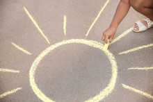 Little Child Drawing Sun With Chalk On Asphalt
